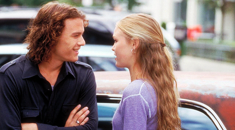 A still from '10 Things I Hate About You'. A young man and woman (played by Heath Ledger and Julia Stiles) are talking to each other at a parking lot.