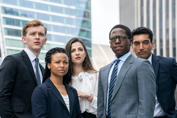 A still from the TV show 'Industry. 5 young 20-somethings are seen dressed in business wear against a city skyline backdrop, they are all looking towards something off-camera.
