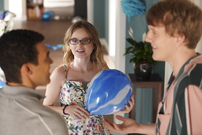 Kayla Cromer as Matilda in Everything's Gonna Be Okay (2020-). Matilda is wearing a floral sundress, glasses, and is holding a blue and white balloon. Two boys stand in front of her having a conversation.