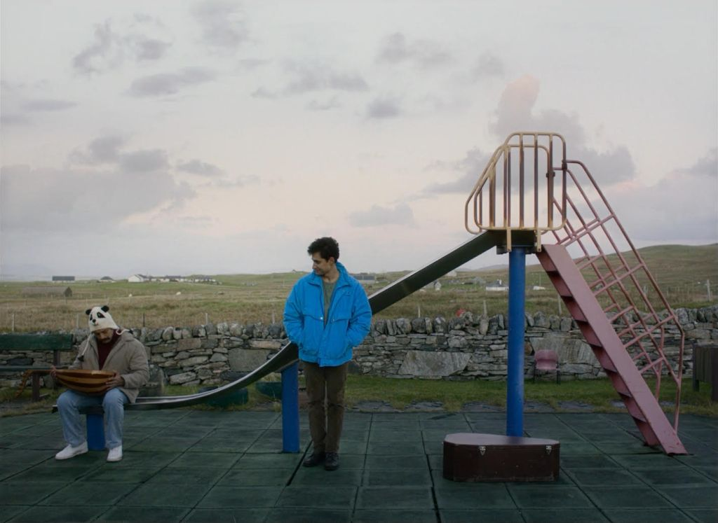 A still from 'Limbo'. Two men are seen at an empty children's playground in the countryside. One man is sitting down on the end of a slide, looking down at his instrument, while wearing a panda hat, beige jacket, jeans, and white trainers. Another man is standing to his right and looking at him while he wears a bright blue jacket, brown trousers, and black shoes.