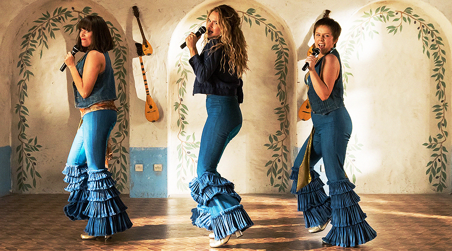 A still from 'Mamma Mia! Here We Go Again'. Young Donna And The Dynamos (played by Jessica Keenan Wynn, Lily James, and Alexa Davies) are dancing and singing in a Greek restaurant.