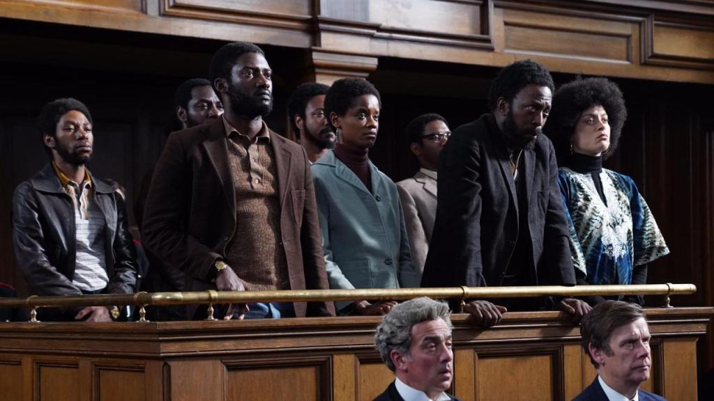A still from 'Mangrove'. Several people are standing in the accused section of a court room, while two lawyers stand below in front of them. Darcus (Malachi Kirby) is on the left, he has a beard, and wears a brown shirt and dark brown blazer, Altheia (Letitia Wright) looks concerned and wears a dark brown turtleneck and light turquoise coat, beside her, Frank (Shaun Parkes) leans forward and has a beard and wears a black blazer, while on the right Barbara (Rochenda Sandall) wears a black turtleneck and a patterned blue dress.