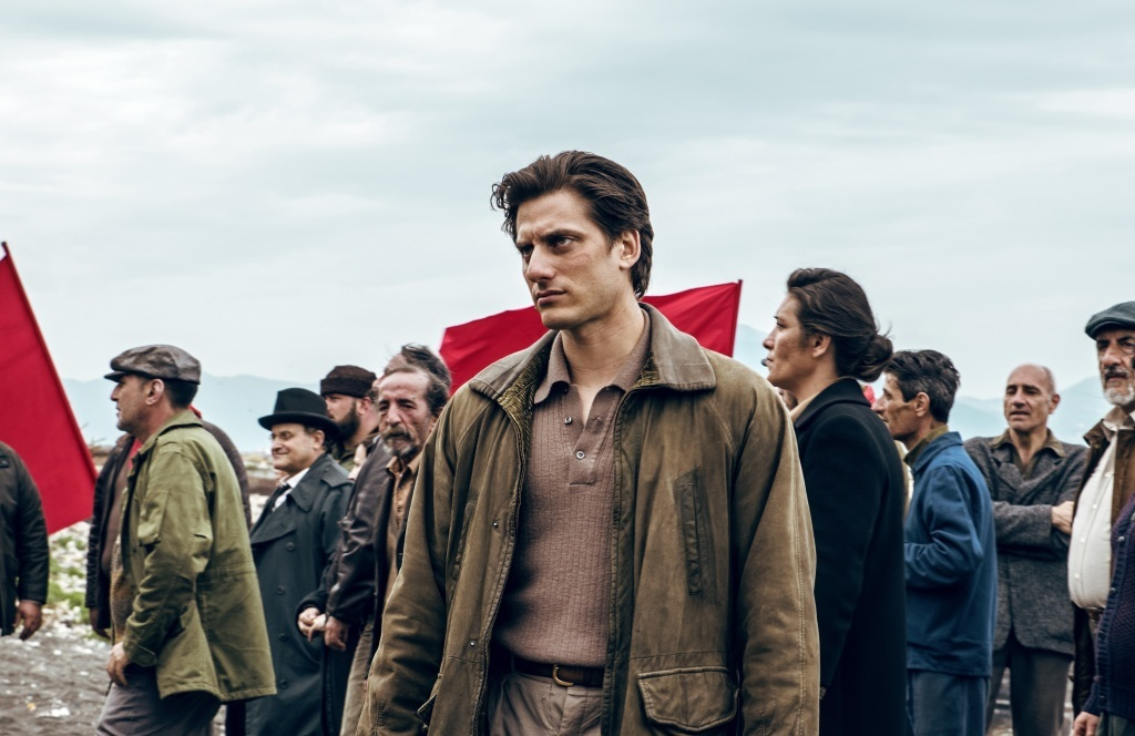 A still from 'Martin Eden'. Martin (Luca Marinelli) is standing with a serious gaze in front of a crowd of people waving red flags. He wears a light brown shirt, a dark beige jacket, and light beige trousers.