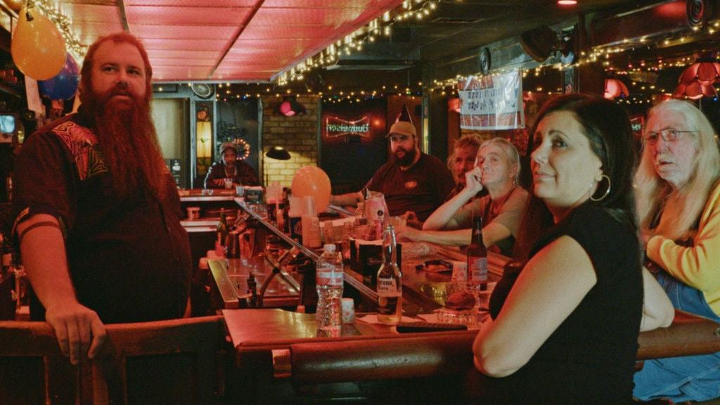 A still from 'Bloody Nose, Empty Pockets'. Several people are seen inside a red lit bar with fairy lights on the ceiling. The barman and customers are staring at something on the left hand side of the shot, bottles and balloons are placed all over the bar.