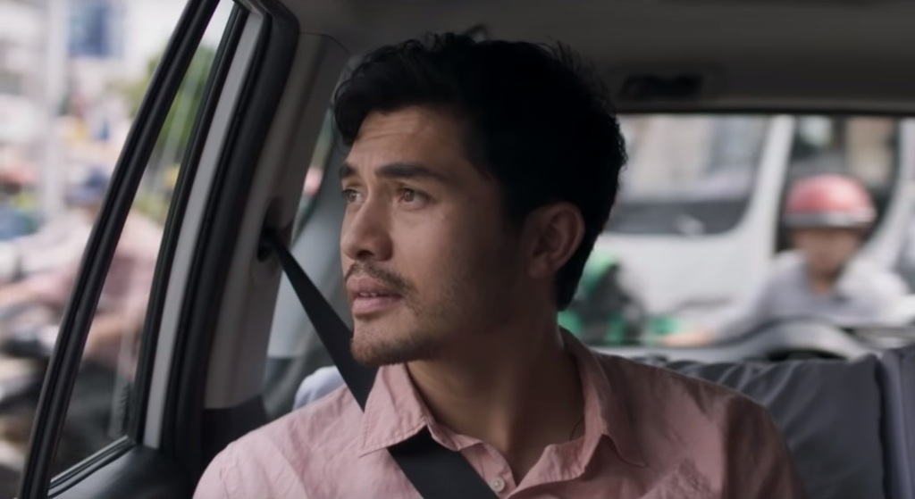 A still from 'Monsoon'. Kit (Henry Golding) is sitting in the back of a car and looking out of the window. He is wearing a salmon coloured shirt.
