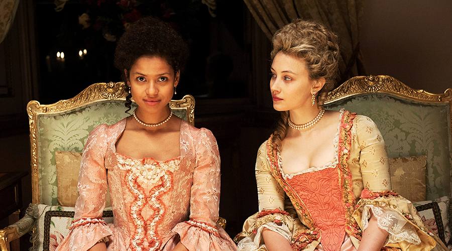 A still from 'Belle'. Two women (played by Gugu Mbatha-Raw and Sarah Gadon) are sitting down next to each other and wearing period dresses.