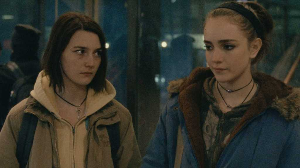 A still from 'Never Rarely Sometimes Always'. Two young women are standing next to each other. Autumn (Sidney Flanigan) is on the left and wearing a necklace, light yellow hooded pullover, and a dark beige jacket. Skylar (Talia Ryder) is wearing her hair up with a headband, several necklaces, a dark patterned sweatshirt, and a hooded blue jacket with faux fur lining.