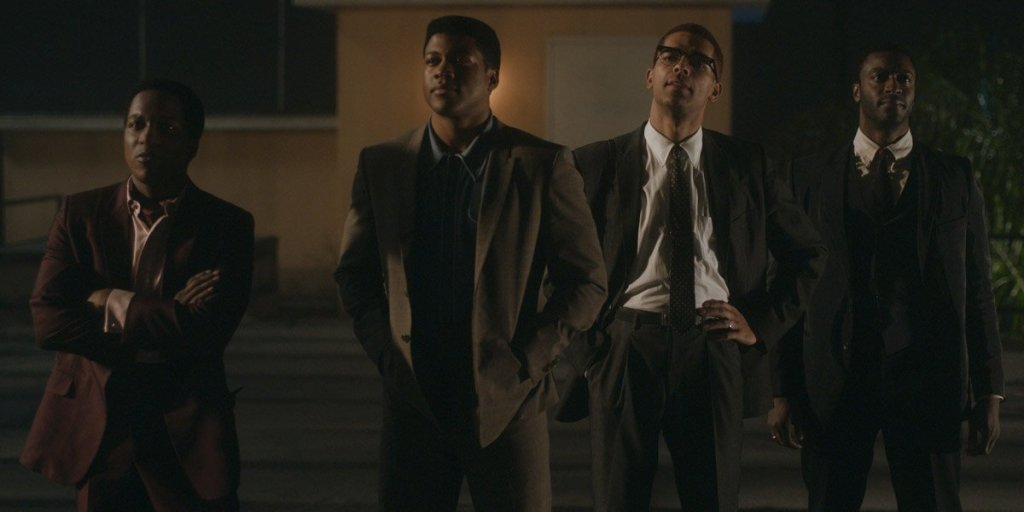 Four young African-American men - Malcolm X, Muhammad Ali, Jim Brown, and Sam Cook - are standing outside a motel.