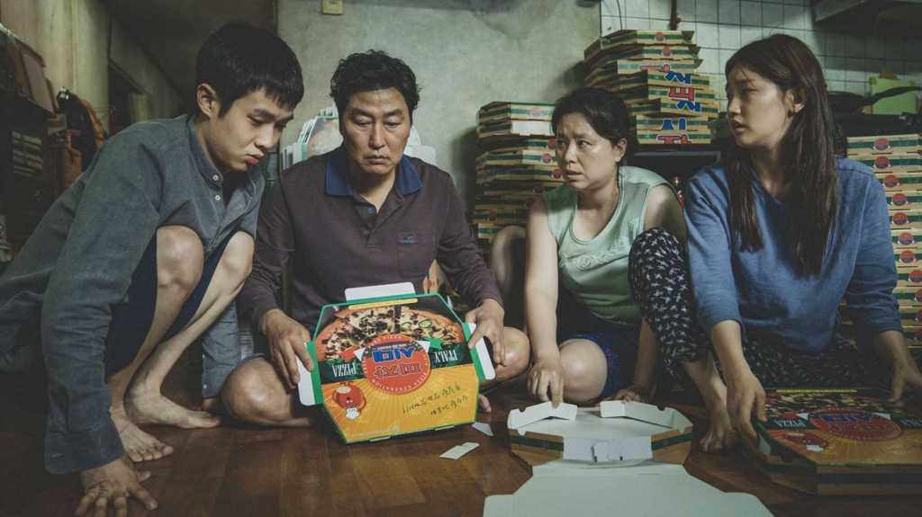 A still from 'Parasite'. A family of four are sitting on the floor and looking concerned as they try to fold pizza boxes. The son is a young man and is wearing a dark grey shirt and navy shorts, his father is wearing a dark brown shirt and is holding a pizza box, the mother is wearing a light green sleeveless top and blue shorts, and the daughter who is also a young adult is wearing a blue shirt and patterned black bottoms.