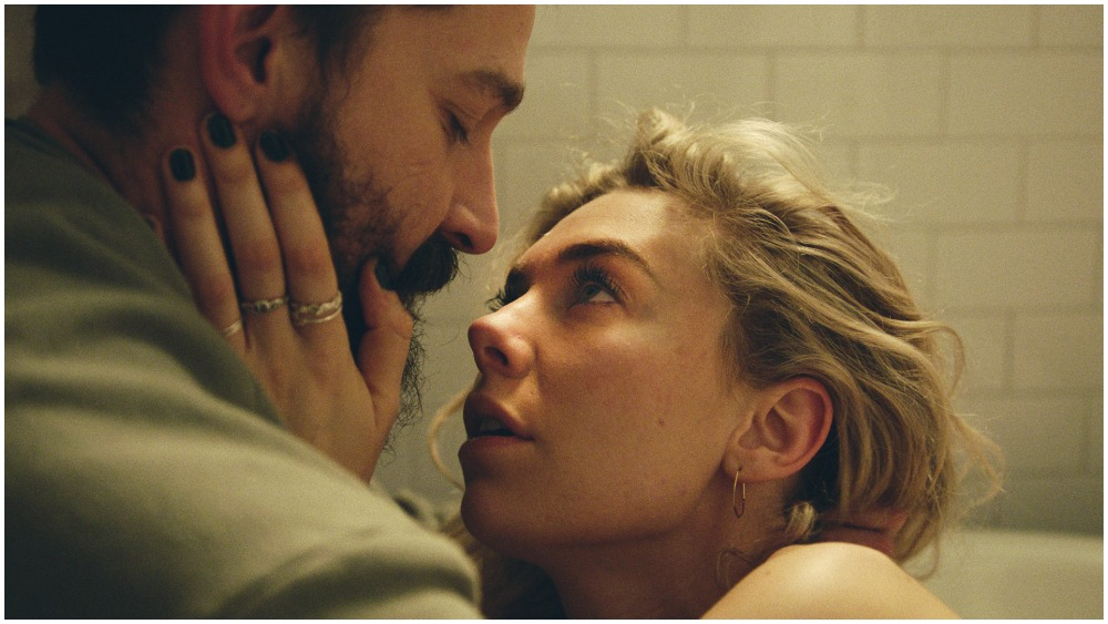 Close up shot of Vanessa Kirby holding onto Shia LaBeouf's face, they are in a white bathroom and looking intensely at each other.