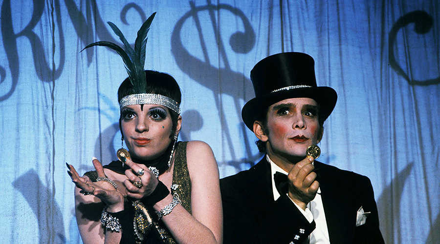 A still from 'Cabaret'. A woman and a man (played by Liza Minnelli and Joel Grey) are wearing 1920s party outfits and holding gold coins.