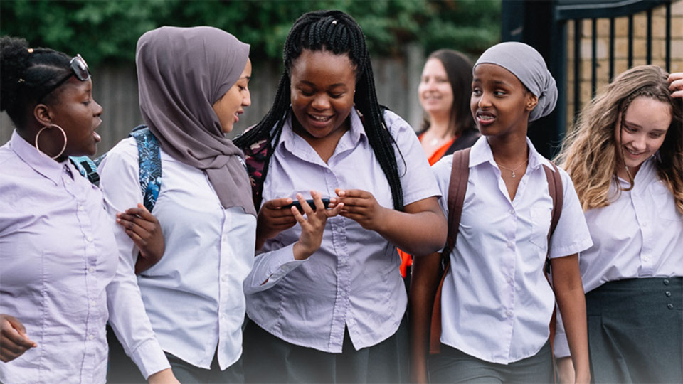 A still from 'Rocks'. Five schoolgirls are walking together looking amused as the three of them observe something funny on a mobile phone. The girls are wearing light lilac shirts and dark grey bottoms, Khadija (Tawheda Begum) on the left wears a dark grey hijab while Sumaya (Kosar Ali) on the right wears a turban-style hijab in light grey.