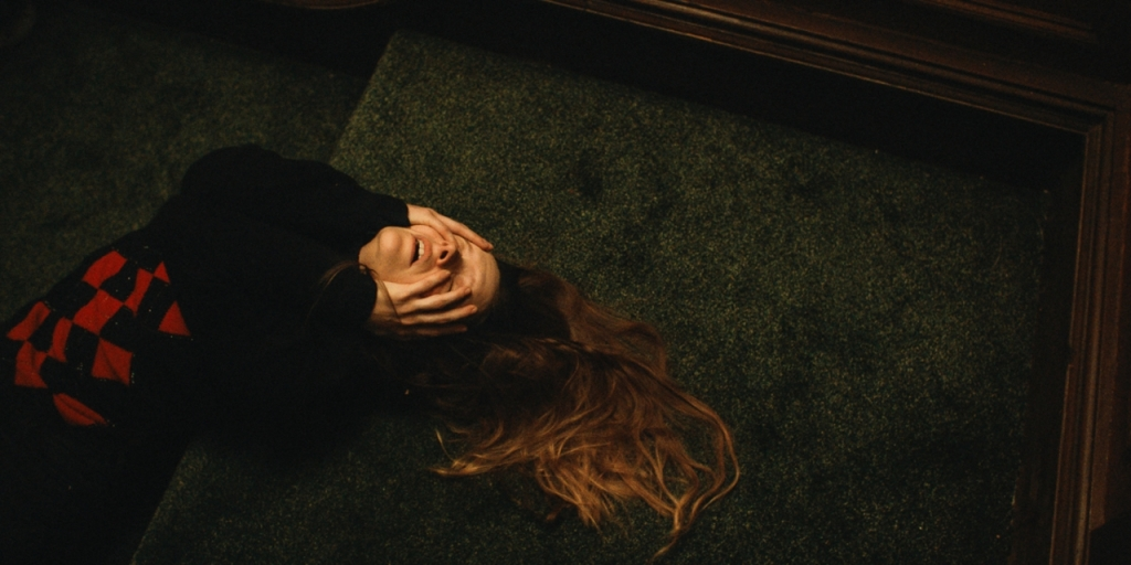 Shot from above, Maud leans backwards on green carpeted stairs. She is lying against the steps with her body pushed up, hair fanned out behind her as she holds her hands up to her face.