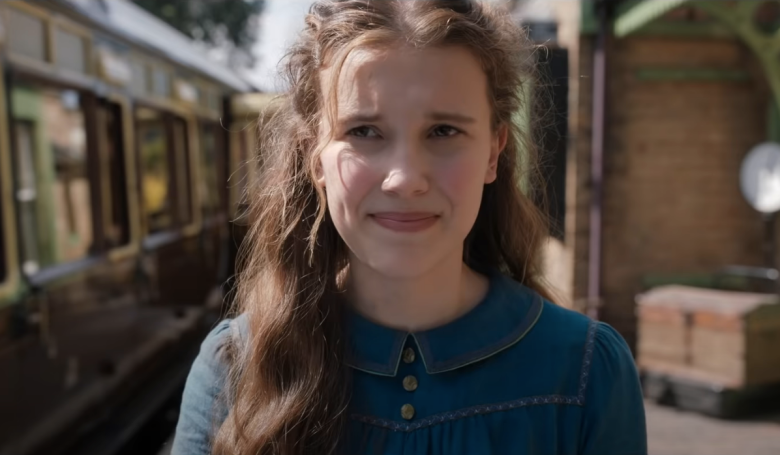 Millie Bobby Brown as Enola Holmes. She stands at a train station, wearing a blue collared dress and her hair is wavy and tousled.