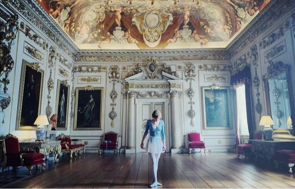 Diana is dressed in a blue ballet leotard and white chiffon skirt. She places her feet in third position, standing at the centre of a large ornate room in the palace.