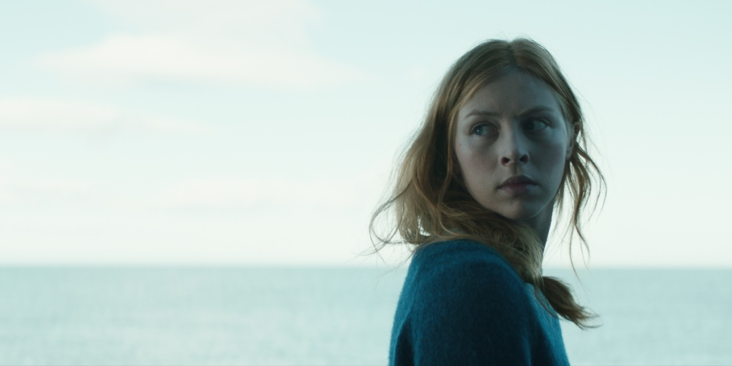 A young woman looks back over her shoulder, looking worried at an unseen presence. The light is grey-blue and in the background, a dull sea merges with the sky.