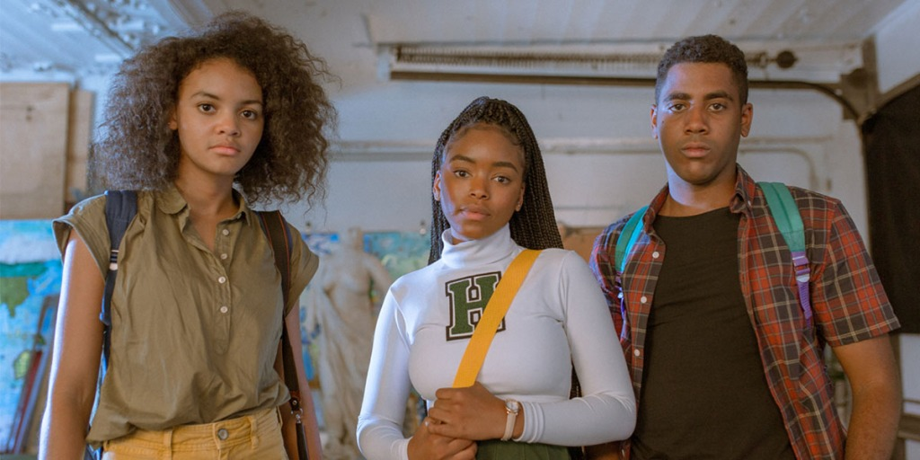 Three young people, two young women and a man who are all African-American, look directly at the camera. The central character, Selah, is wearing a high school cheerleader outfit in green and white. Her gaze is confident and she has perfectly groomed eyebrows.
