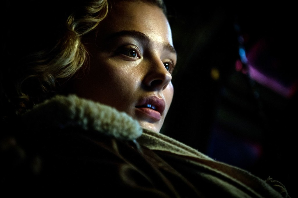 Chloe Moretz as Maude in 'Shadow in the Cloud'. A close up on Maude in darkness, her face illuminated slightly. She stares off to the right of the frame, mouth slightly open as if in wonder.