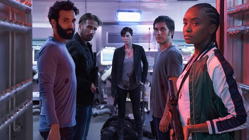 A still from 'The Old Guard'. A group of five people are standing in an industrial space, looking towards the camera. Sebastian (Matthias Schoenaerts) and Nile (Kiki Layne) are holding large rifles, while Andy is holding a gun and wears a blood stained shirt as she stands over a dead body.
