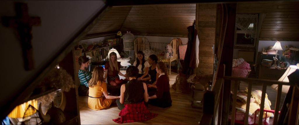 A scene from 'The Sinners'. A group of 7 teenage girls are sat in an attic bedroom in a circle, holding hands and chanting. The image is shot from the top of the room, a crucifix just visible in the top left corrner. The room is filled with twee paraphanelia such as a cot, viking horns, a bird cage and piles of blankets. The walls are largely wooden giving the house and old style feel.