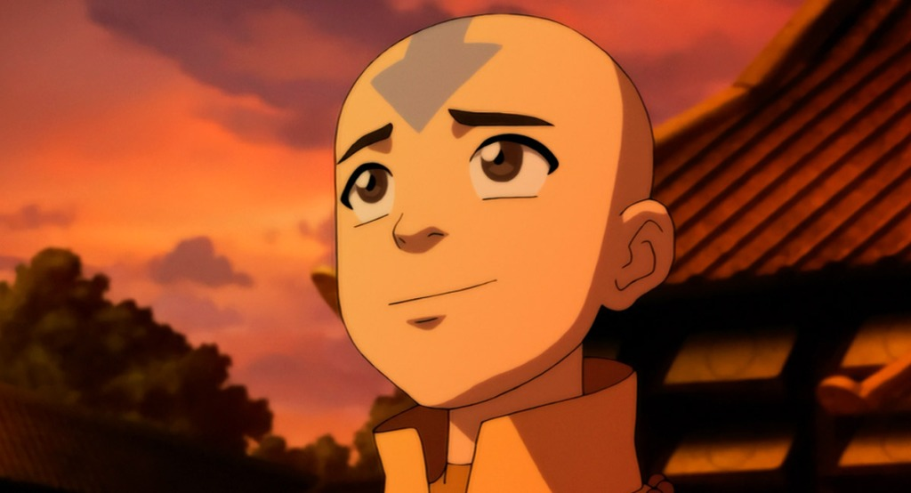 A close-up shot of Aang, a young boy with a bald head and a blue arrow that points down his forehead. The background is a pink cloudy sunset and he looks up to the sky, seeming hopeful.