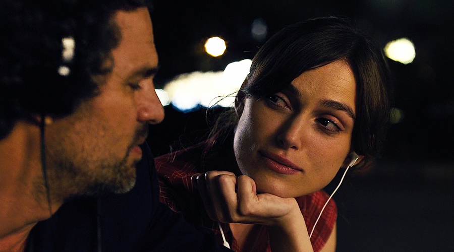 A still from 'Begin Again'. A man and a woman (played by Mark Ruffalo and Keira Knightley) are both listening to music via their headphones and staring sweetly at each other.
