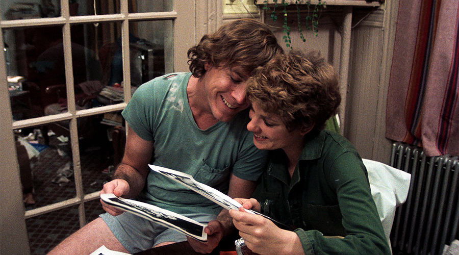 A still from 'Between The Lines'. A man and woman (played by John Heard and Lindsay Crouse) are sitting next to each other and laughing at photographs.