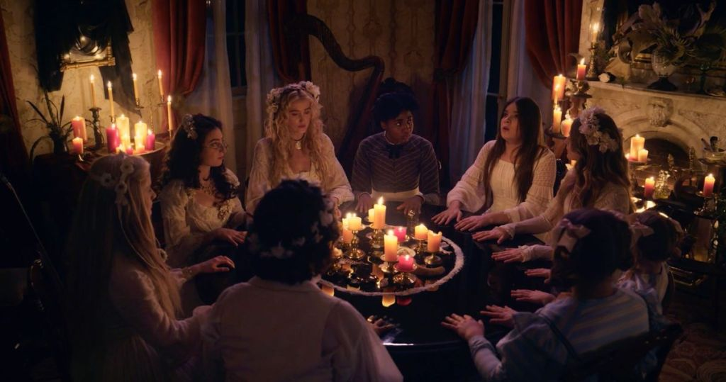 A still from Season 2 of 'Dickinson' Emily and he sister and friends sit around a table set up for a seance. Salt around the edges and a ton of candles are lit. All the ladies are in their white night gowns.