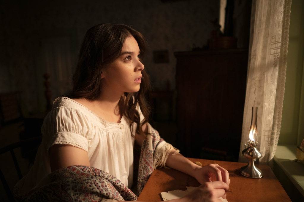 Hailee Steinfeld as Emily Dickinson in 'Dickinson'. She is in her white night gown as she sits at her desk. She gazes out the window as she writes.