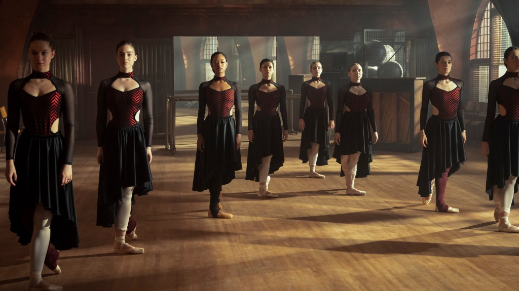 Eight ballet dancers stand in a formation in a practise room, a large mirror behind them as light streams in from the windows. They are all dressedd in long black skirts, hitched up on one side, and cut out leotards with black and red zigzags.