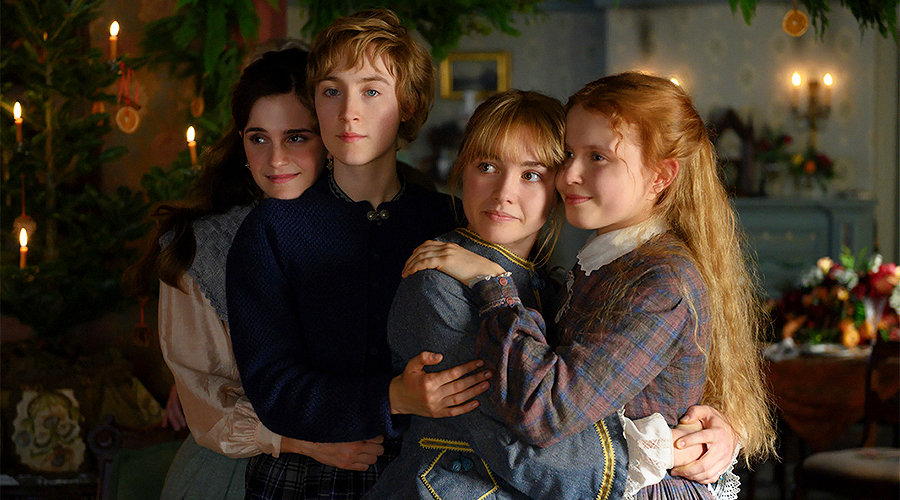 A still from 'Little Women'. Four young women (played by Emma Watson, Saoirse Ronan, Florence Pugh, and Eliza Scanlen) are embracing each other and smiling.