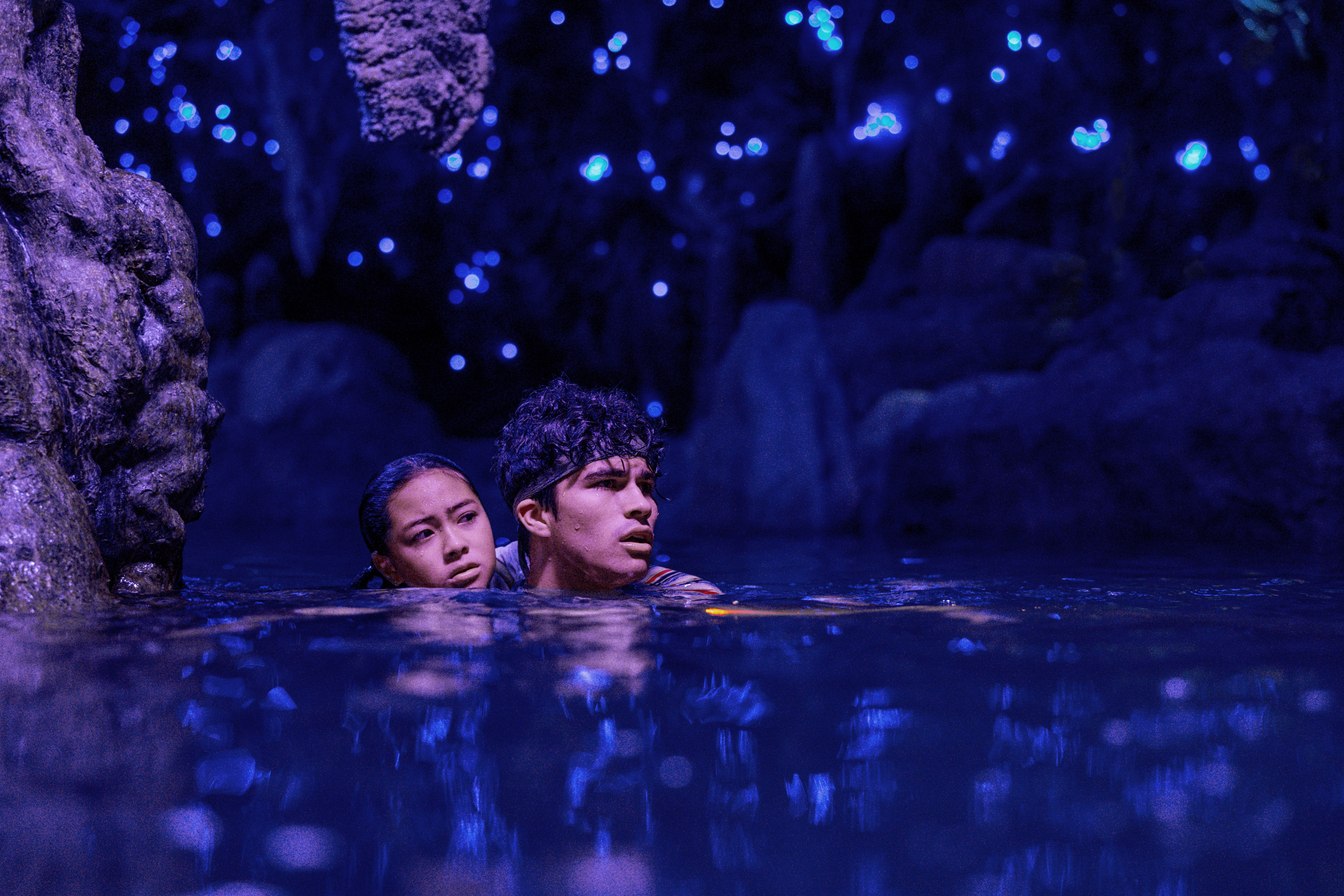 KEA PEAHU as PILI, ALEX AIONO as E in FINDING 'OHANA. Pili holds on to E as the swim in water in a luminescent cave.