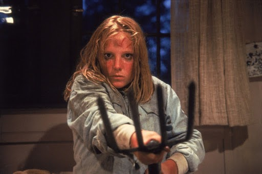 A still from 'Friday the 13th Part II'. Ginny is shown centre frame, in close-up, wielding a pitchfork to the camera. Her ginger hair is wet with sweat and clinging to her face, mascara is running down her face. She is in danger,