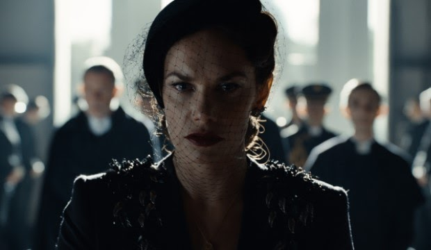 A still from 'His Dark Materials' Season 2. Mrs. Coulter (Ruth Wilson) is shown in close-up, centre frame wearing black funeral dress, including a veil. Her pale face is wet with tears and a dark plum coloured lipstick stands out in the dark image.