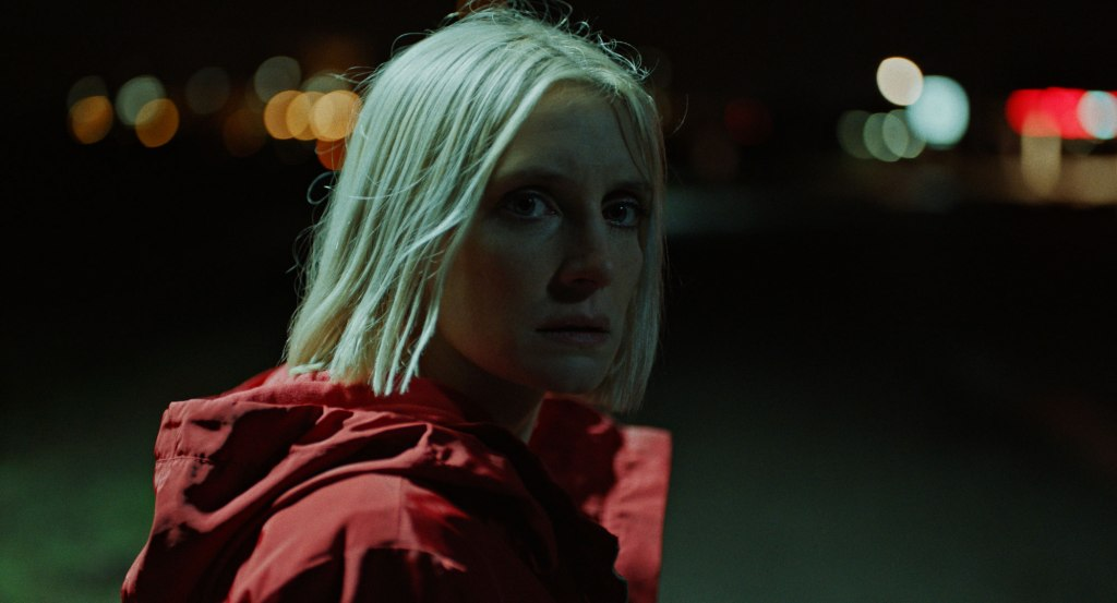 A still from 'Hunted'. Eve (Lucie Debay) is shown in close-up, to the left of the image. She is looking back over her shoulder. It is night, the image is lit only by blinkered street lights in the background. Eve is wearing a red raincoat, in her late 20s and has chin length platinum blonde hair and a sharp nose. She looks scared.