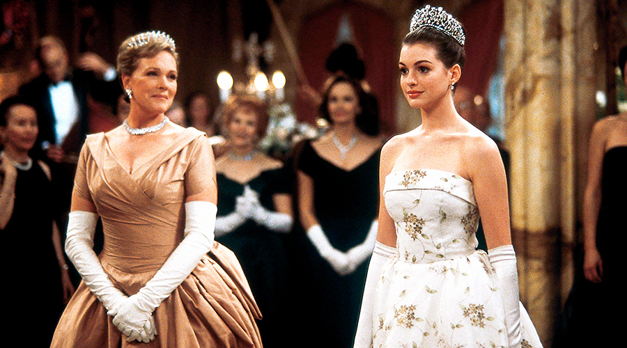A still from 'The Princess Diaries'. An older woman and young woman (played by Julie Andrews and Anne Hathaway) are standing at the centre of a formal event, both wearing royal gowns and tiaras.