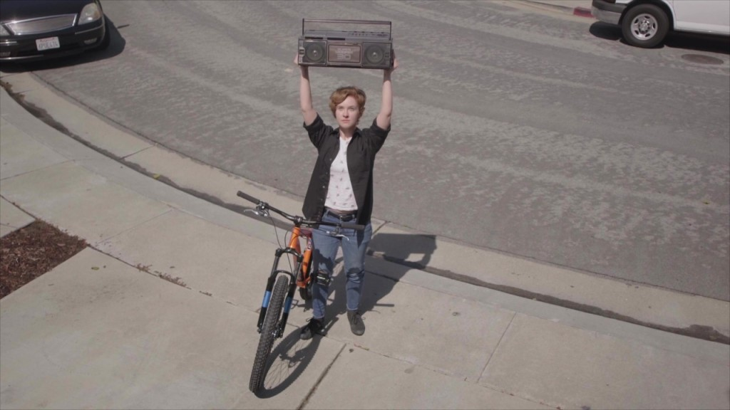A still from short film 'Lovergirl'. A young white woman stands on  a footpath with her bike leaning against her. She is holding a boombox above her head, mimicking the famous scene from 'Say Anything'. She wears blue jeans, a white t-shirt and open black shirt. Her hair is ginger and cropped short.
