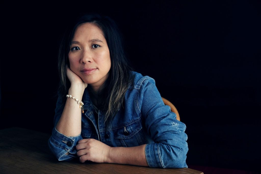 A press shot of director Roseanne Liang, wearing a denim jacket and resting on a table with her face propped up on her hand.