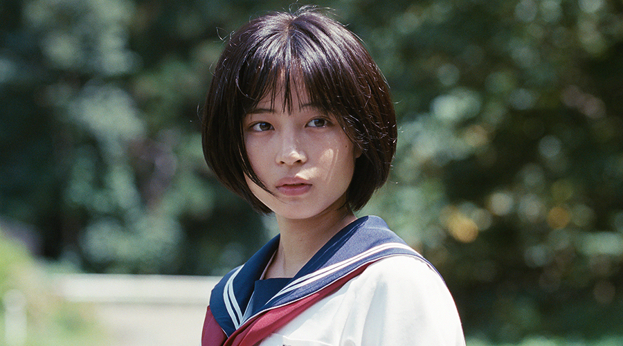 A still from 'Our Little Sister'. A young girl (played by Suzu Hirose) is wearing a Japanese school girl outfit and staring afar.