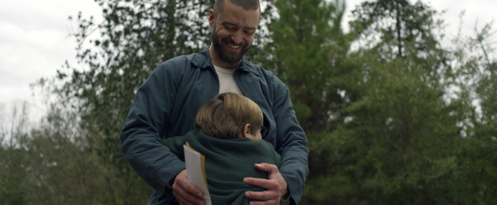 Justin Timberlake as Palmer and Ryder Allen as Sam in 'Palmer'. Sam gives Palmer a hug, who appears to have mail in his right hand while his left is gently placed on Sam's back. Palmer smiled down at Sam. There are trees behind them.