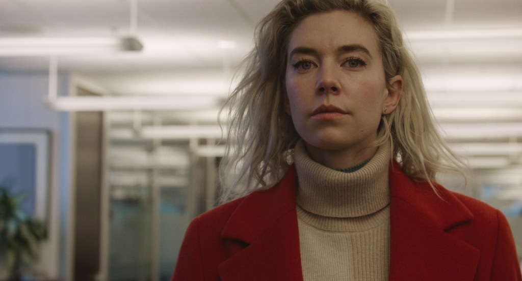 A still from 'Pieces of a Woman'. Martha (Vanessa Kirby) is shown in close-up walking through the bright lit corridors of what appears to be a hospital. She is wearing a beige polo neck jumper and a red wool coat. She is a lagte 20s/early 30s white woman with dark eyebrows and pale skin. Her hair is shoulder length and blonde with grown out roots. She looks determined.