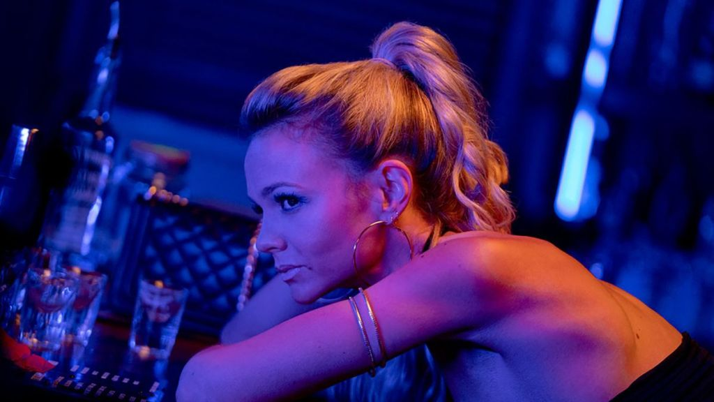 Carey Mulligan as Cassie in 'Promising Young Woman'. She leans against a bar on a under blue/purple/yellow neon lights. She wears a sleevless black dress, a gold arm band, gold hop earrings, and has her blonde hair in a loose high-ponytail.