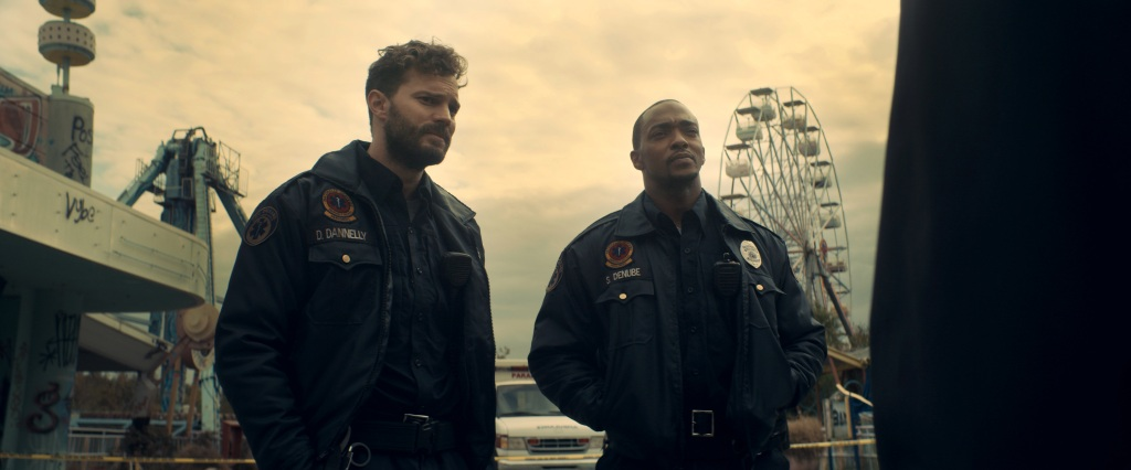 A still from 'Synchronic'. Dennis (Jamie Dornan) and Steve (Anthony Mackie) are two paramedics, standing in and abandoned fairground in a seedy New Orleans. The rides are covered in grafitti and the sky is dull and yellow tinged. Dennis is a man in his 30s, white with curly brown hair and a full beard. Steve is a man in his 30s, Black, with a shaved head and goatee. Both men are physically fit.