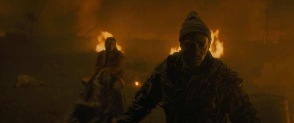 A still from 'Synchronic'. Steve (Anthony Mackie) is shown in mid-shot, to the right of the frame. The image is shrouded in fire and smoke, Steve is running away from a female figure perched on a rock, it is unclear who she is surrounded by the flames, but she appears to be a threat.