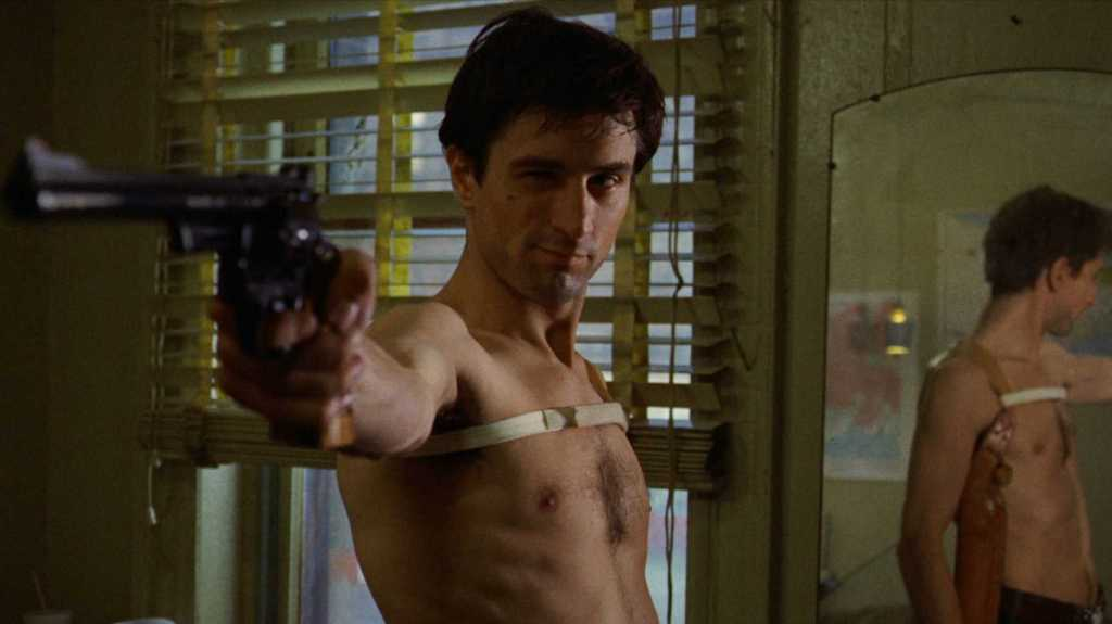 A still from 'Taxi Driver'. Travis Bickle (Robert DeNiro) is stood centre frame, shirtless, holding a gun of which he is looking down the barrell. His expression is almost a smirk.