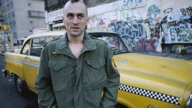 A still from 'Taxi Driver'. Travis Bickle (Robert DeNiro) is pictured standing on the roadside in front of his taxi. The New York City streets are covered in graffiti. He is wearing a green military jacket, his head shaved with nothing but a dark strip on hair down the middle, he face is pulled into a scowl.