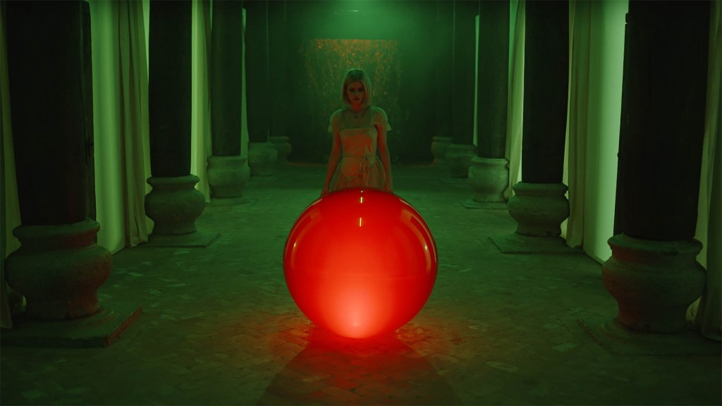 Carlson Young in The Blazing World. Margaret, wearing a white dress, stands in the centre of a room lit bright green, with tall pillars lining each side. In front of her is a glowing red sphere about waist height, which she looks down at with curiosity.