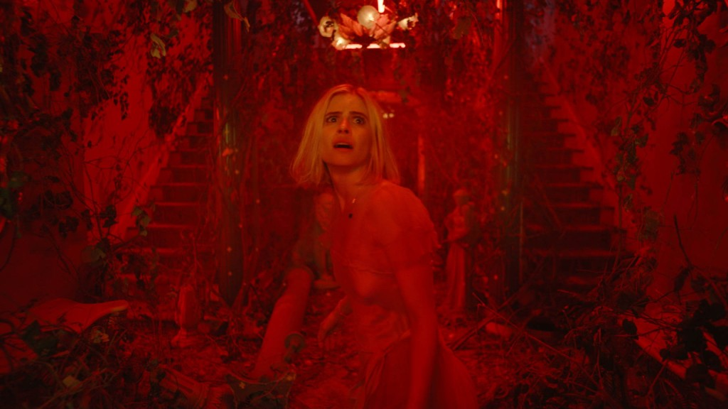Carlson Young in The Blazing World. Margaret, a young white woman with short blonde hair, is centre frame, staring off to the top right of the camera with a terrified expression. The whole shot is flooded with bright red light, and the room behind her has two staircases ascending either side, with everything covered in overgrown ivy.