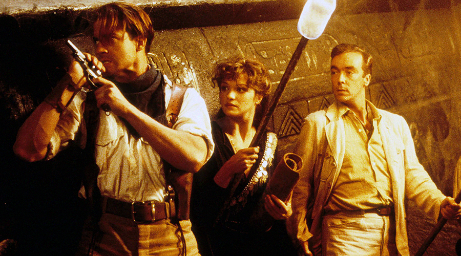 A still from 'The Mummy'. Two men and a woman (played by Brendan Fraser, Rachel Weisz, and John Hannah) are holding guns and old torches.