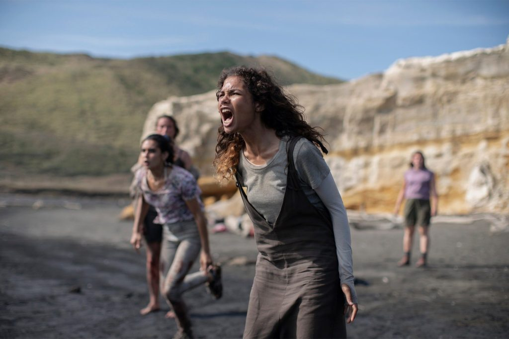 A still from TV show 'The Wilds'. Nora (Helend Howard) is shown centre frame, in a long shot. She is a young woman of colour with long dark curly hair, and she is screaming. She is wearing a grey long sleeve top and a darker grey pinafore dress. She is standing on the shore of a beach and three other similarly aged girls stand behind her, one of them is running,